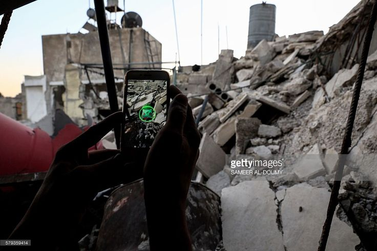 A Syrian gamer uses the Pokemon Go application on his mobile to catch a Pokemon amidst the rubble in the besieged rebel-controlled town of Douma, a flashpoint east of the capital Damascus on July 23, 2016. / AFP / Sameer Al-Doumy        (Photo credit should read SAMEER AL-DOUMY/AFP/Getty Images)