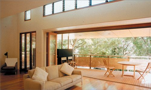 A contemporary living room has wide glass bifold doors opened to connect the room to an outside balcony with trees beyond. High windows with...