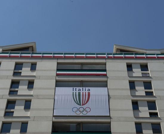 """Il villaggio olimpico di Londra si sta popolando e ogni squadra, al suo arrivo, appende la propria bandiera ai balconi delle palazzine. A metà tra goliardia e sfida, la """"battaglia delle bandiere"""" viene portata avanti nelle più svariate maniere"""