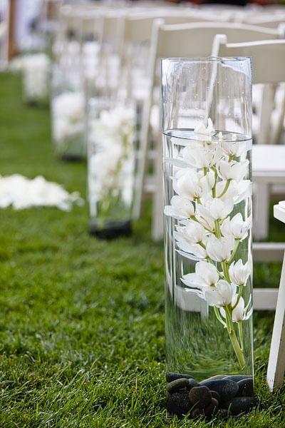 The ceremony aisle will feature varying heights of cylinder vases with submerged white tulips, white stock flowers, and ivory spray roses.