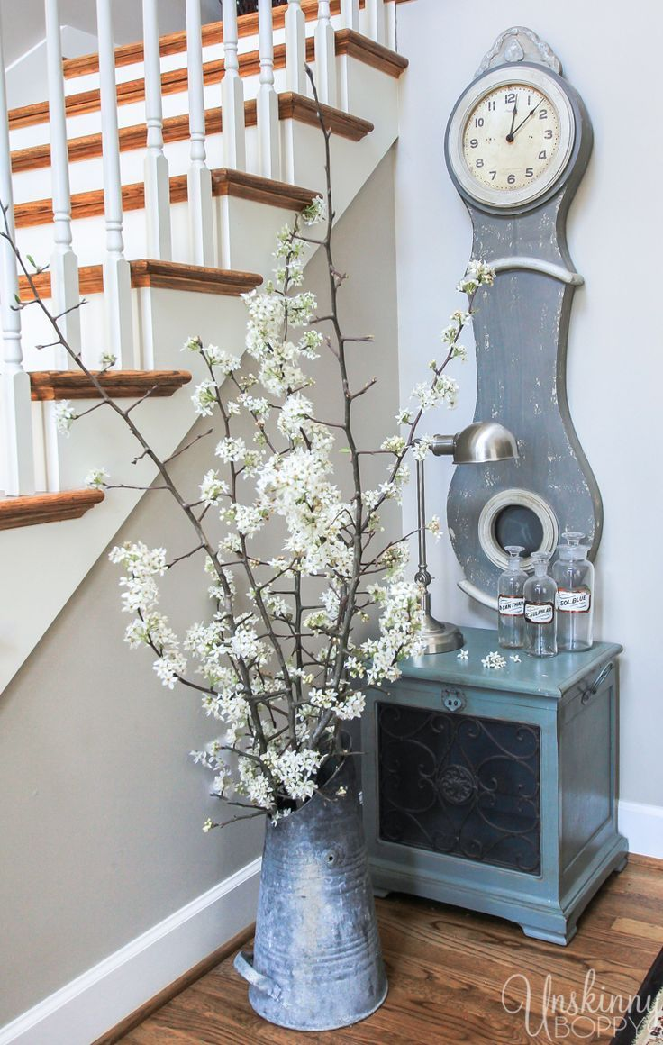 Pretty Spring home decor ideas- Mora swedish clock and a coal bucket full of blooms.