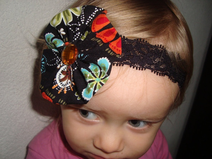 Skinny ( 1 inch) comfortable stretchy Lace elastic headband with a  super sweet black multicolor fabric flower. Flower measures about 2 inches.    Can