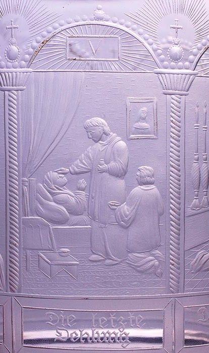 """Detail - Číše s vyobrazením Sedmi svátostí. Čechy, Jablonec nad Nisou, řezal Anton Simm, kolem 1830. Silnostěnná válcovitá číše z broušená čiré skloviny s laločnatým okrajem a radiálně uspořádanými řezy na spodní straně, plášť s náročně řezaným religiózním námětem sedmi křesťanských svátostí, v obloukovitých arkádách jsou provedeny řezby ilustrující jednotlivá znamení zprostředkující boží milost s příslušným textem, signováno v sedmém poli vpravo dole """"AS"""". Stav A, v. 16,2 cm. Anton Simm…"""