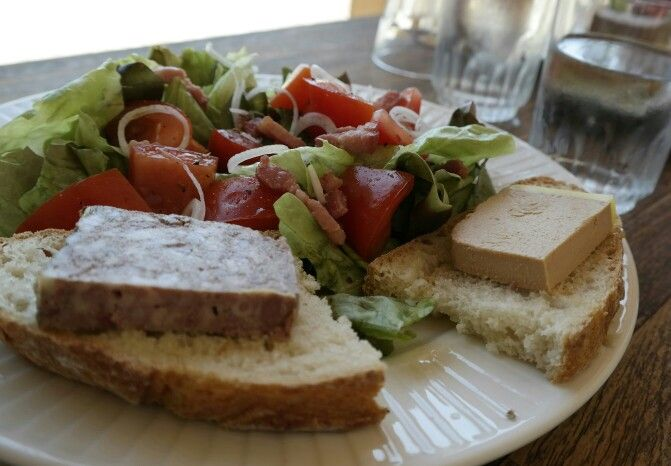 Salad with unions, tomato, bacon, accompanied with terrine de campagne and mousse de canard on bread.