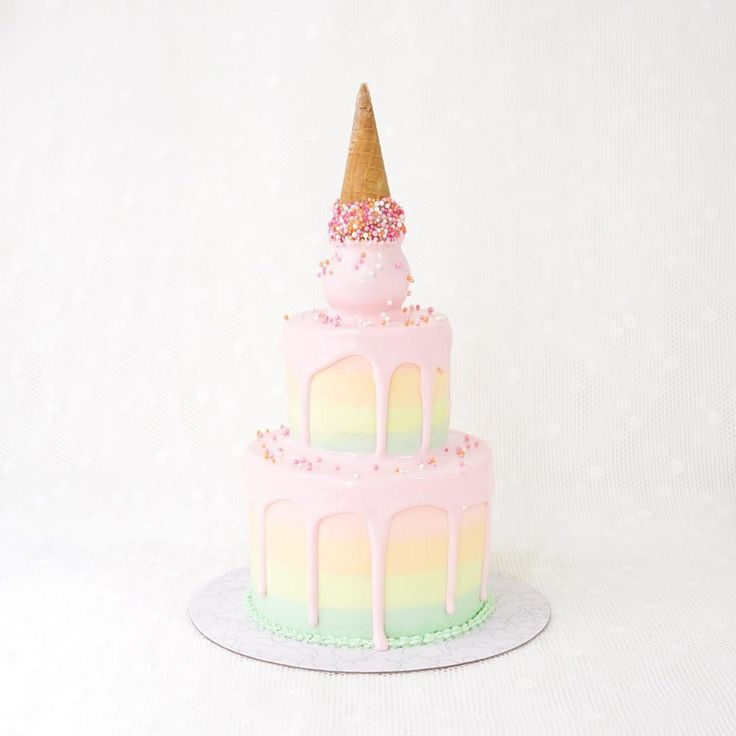 Tiered wedding cake in pastel rainbow colors and an upside down ice cream cone // Beautiful cake inspiration