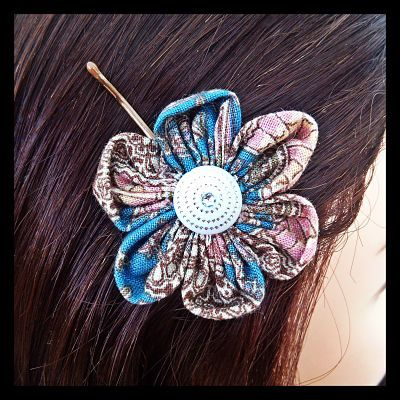 Hand stitched oriental print fabric flower on a bobby pin. The Japanese garden print on this hand stitched fabric flower features shades of dusty pink, blue and beige, pleasantly adorned with an ornate centre piece. 20 Available. $8.50 each.