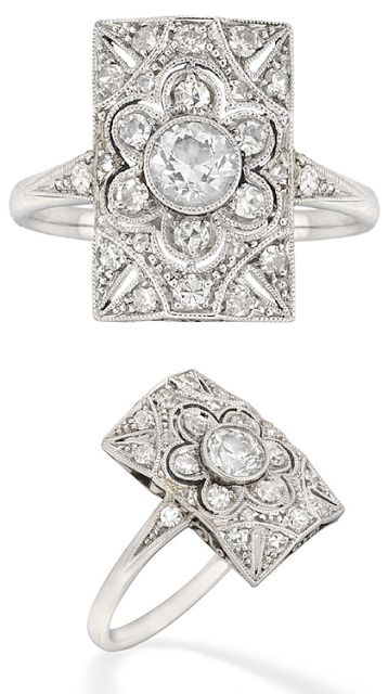 Edwardian pierced tablet cluster ring. Created in 1910, this beauty centers a flower-shaped cluster of old brilliant-cut diamonds, all set in platinum with diamond-set shoulders and pierced scroll gallery. Via Diamonds in the Library.