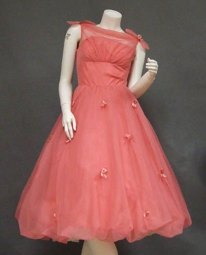 A gorgeous 1950's prom dress in coral nylon. Fitted sleeveless sheer bodice with gathered bust, bow topped shoulders and a set in waist. Attached strapless acetate liner. Dress has a gorgeous full balloon hemmed skirt sprinkled with bows. The skirt is lined in tulle but is shown here with an additional crinoline... not included. Rear metal zipper. Lined in acetate.
