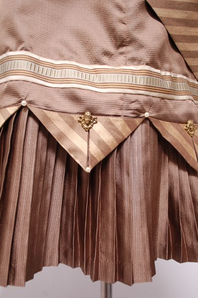 Skirt hem Detail - truly victorian | Wearing History. Horizontal tucks with brown triangles above vertical pleats.