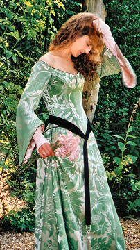 """""""A figure-enhancing two-piece gown, shown in a stunning green and silver silk damask - lightly corseted with back lacing. Inspired by the paintings of John William Waterhouse, this Pre-Raphaelite-style wedding dress has fitted ruched chiffon undersleeves with button detailing at the wrist. These are revealed beneath classic trumpet-shaped 'medieval' sleeves."""""""
