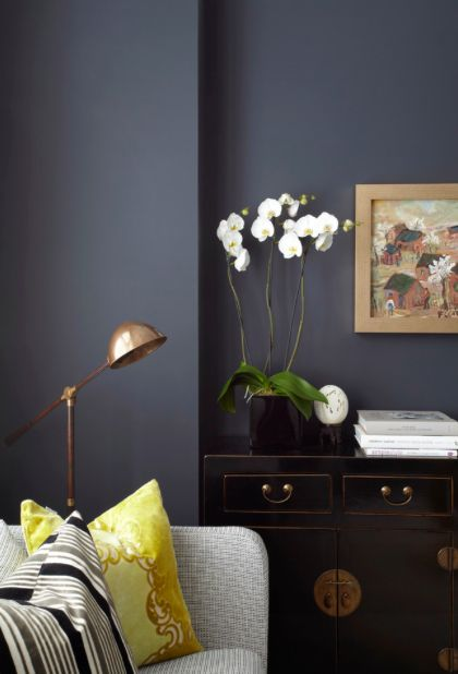 Copper lamp, deep grey walls and light furniture set the mood in the living room.