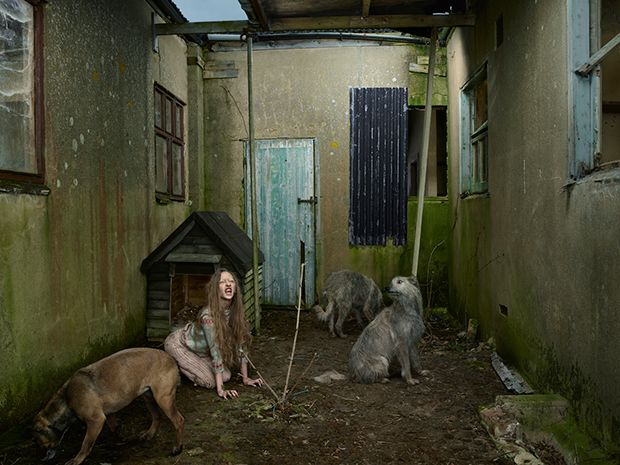 """DARK, DISTURBING PHOTOS ILLUSTRATE STORIES OF 'FERAL CHILDREN'.  Oxana Malaya, Ukraine, 1991. Found living with dogs in a kennel, her alcoholic parents left her outside when she was three years old, where she curled up with mongrel dogs, which probably saved her life. Found when she was EIGHT years old, she behaved like a dog and only knew the words """"yes"""" and """"no"""".  Yes, people SUCK.  London-based photographer Julia Fullerton-Batten uses these photos to tell the stories of these feral…"""