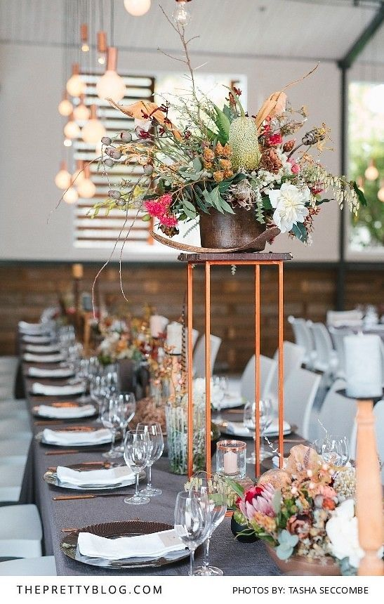 a tall stand in the centre of the table with a raised botanical/indigenous arrangement, with candles below and several smaller arrangements to the sides of the square table