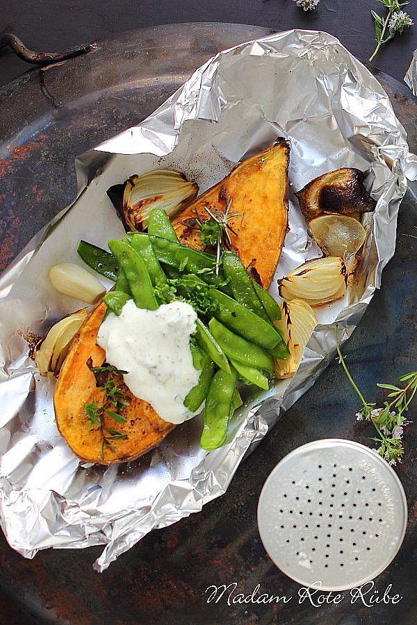 Vegetarisches Gemüsegericht mit frischen Zuckererbsen auf ofengebackener Süßkartoffel mit Zwiebeln, mediterranen Kräutern und pikanten Dip.