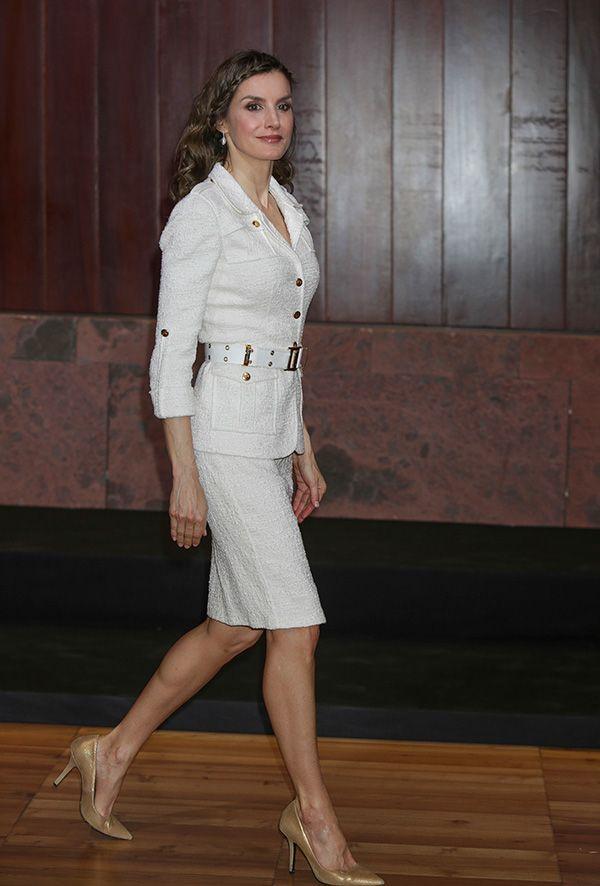 La Reina con el traje de chaqueta compuesto por sahariana y falda lápiz en 'bouclette'. Está firmado por Felipe Varela, y unos salones dorados de Uterqüe.