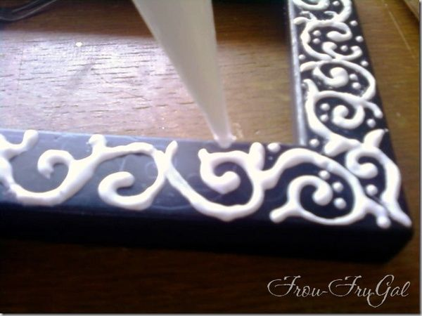 DIY: Dress up a cheap frame by decorating is with glue, let it dry, and then paint over it with one solid color and it looks like a specialty carved frame!