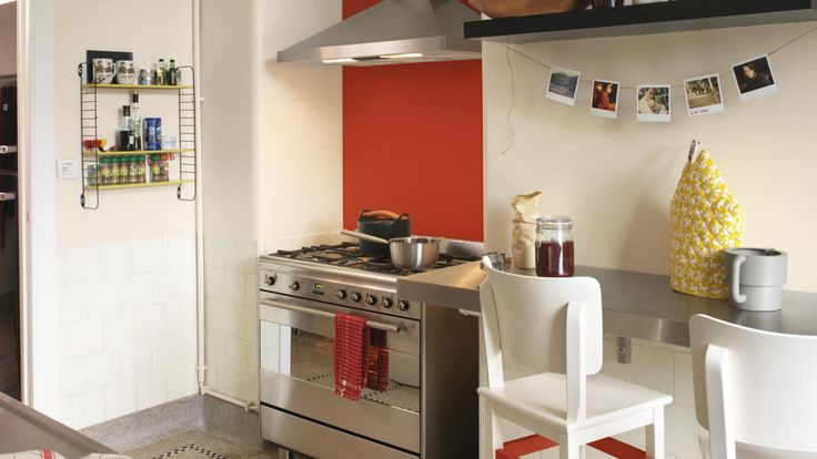 A kitchen with crisp white walls and a red feature wall.