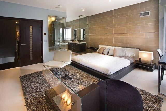 chambre adulte en couleurs terreuses et cheminée moderne