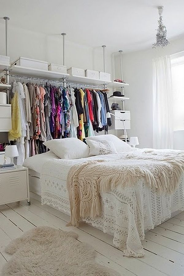 Such a cool idea (if you love your clothes enough to display them like this)!  Dress bar behind the bed.  Good for if you don't have a headboard AND if you have limited closet space.