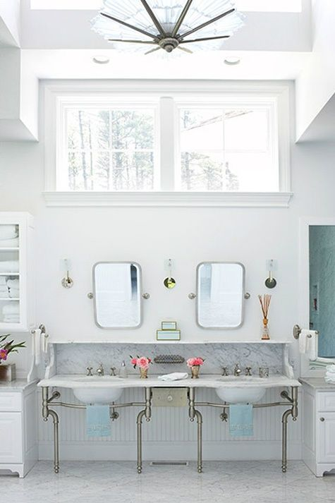 A simple yet contemporary bathroom. Once again we see the double vanities. You can see parts of the built ins on the side of the sinks and the half window gives great natural light while still giving you plenty of privacy from your neighbors. The light fixture is a great addition and really ties in the whole white and metallic theme.