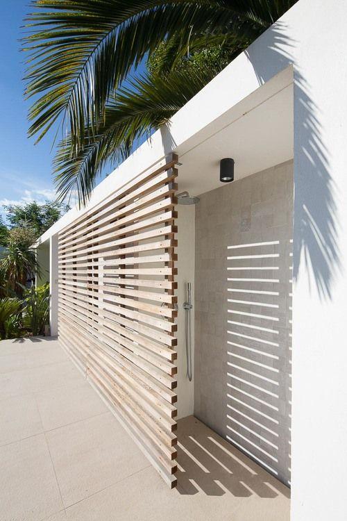 This outdoor shower is hidden behind a wooden slat wall.