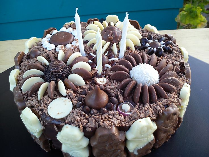 Rich chocolate cake, frosted using chocolate ganache, assortment of chocolates to decorate - ferrero rocher, hershys kisses, cadbury chocolate buttons, m&ms, freddo frogs, crumbled flake, fudge and nestle chocolate morsels :)