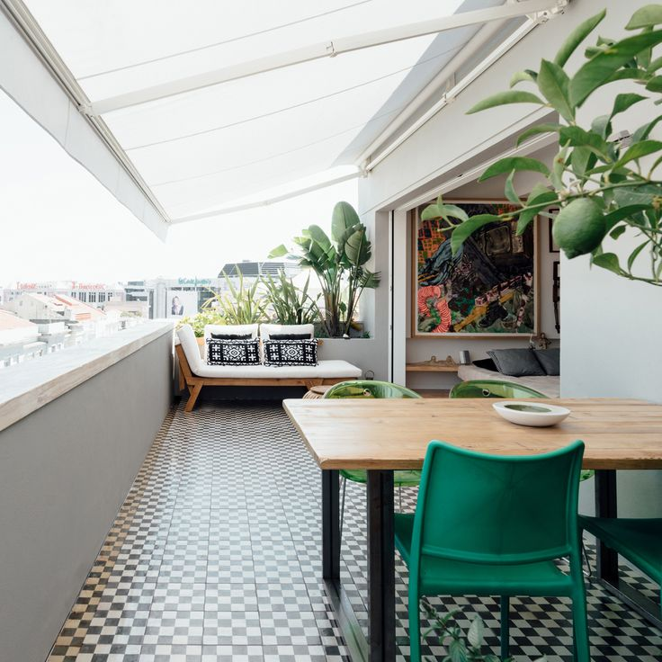 A long social space dotted with green forms one half of this apartment, located in a 1930s neighbourhood in Lisbon and designed by Atelier Data.