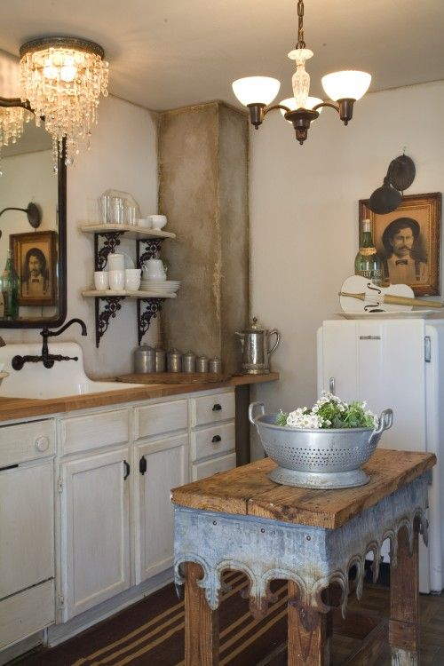 WOW...love theKitchen island detail..love the old photo, mirror & sink, rug and cans :) Cool fridge!