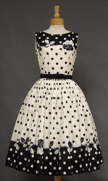 "Striking Black & White Cotton Sun Dress A striking day dress in black and white cotton with a floral and polka dot print. Dress has a fitted bodice and a full skirt (shown here with a crinoline... not included). Matching black belt with square bow. Label reads, ""Jerry Gilden New York."