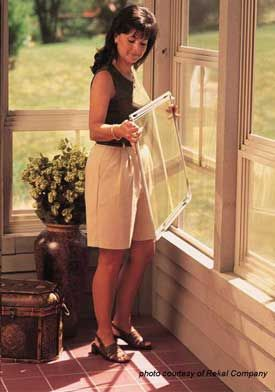 Lady demonstrating use of screen porch windows. These are vinyl windows that are used to turn your screened porch into a three season porch.
