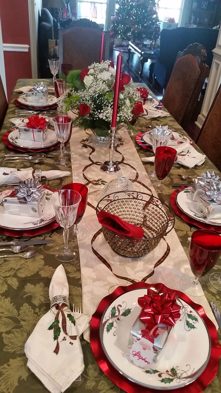"""Christmas 2017, 1 of 2, Green tablecloth with Lenox """"Holiday Nouveau Ribbon"""" runner and napkins and also china.  Red Lenox and Noritake crystal stems. Silver napkin rings and accents; small present at each setting also works as place card. Red scalloped chargers."""