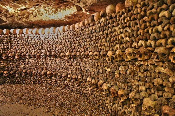 Katakomben von Paris mit haufenweise gestapelter Gebeine und Schädel