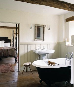 En suite master bathroom with chair rail paneling and timbered ceiling. Simple and clean but with old world charm.