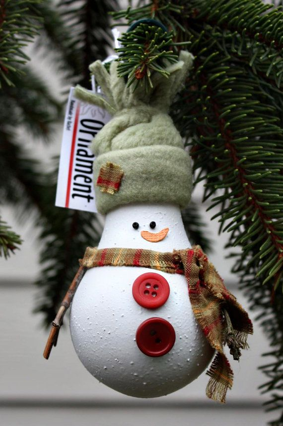 Snowman Christmas Tree Ornament ~ He is made from a recycled light bulb and is painted with a textured spray paint and embellished with a plaid scarf, buttons, stick arms, bead eyes and warm fleece hat. He comes with an ornament hook attached to the top.