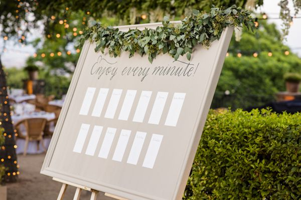 Seating plan en un marco con guirnalda de verde. Boda elegante en el Hotel Miramar en Barcelona. Guirnaldas de luces, iluminación. Seating plan on a frame with greenery garland. Elegant and romantic destination wedding with string lights in Barcelona at Hotel Miramar (Barcelona).
