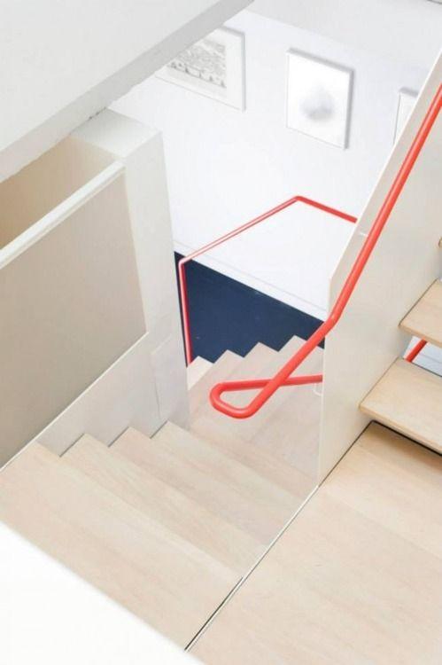 Coole Treppe mit orangefarbenem Handlauf. Ein echter Hingucker im sonst weißen Interieur.