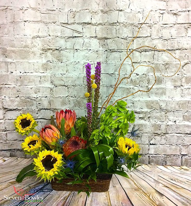 Summer time flower arrangement of sun flowers and protea