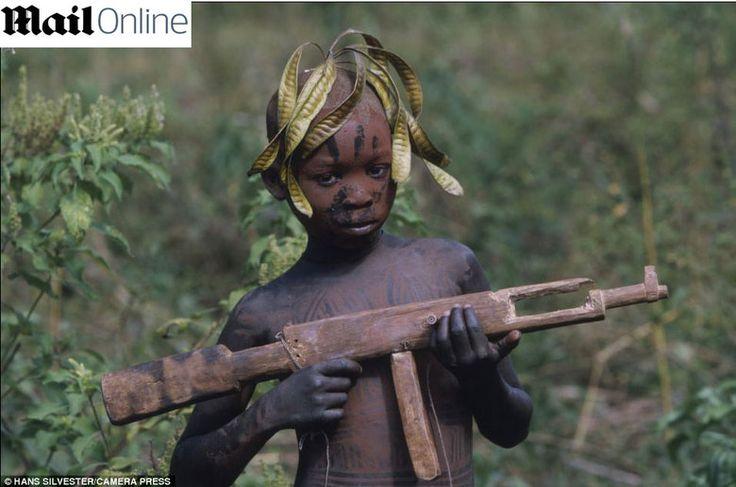 Apesar de terem um estilo de vida nada compatível com o mundo moderno, alguns elementos da civilização já chegaram à tribo. O menino da foto segura uma arma de madeira parecida com um fuzil