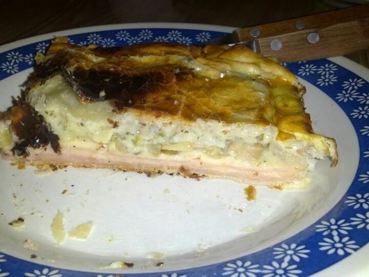 Torta de jamón y queso con salsa blanca.