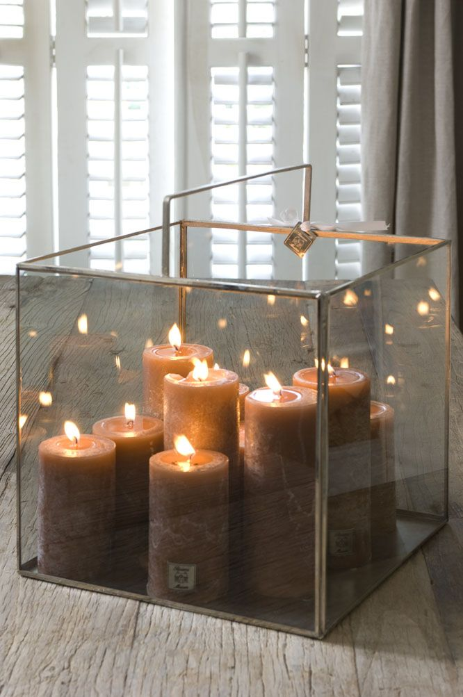 large glass contemporary lantern filled with honey colored candles
