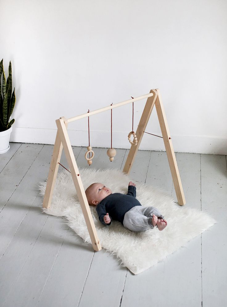 DIY Wooden Baby Gym. NOTE: When your little one has grown out of it it's quite easy to sew two folds on a wide piece of fabric and tuck the legs on the play gym into the folds for a tent!