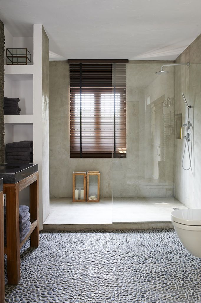 Grey bathroom, cement walls, pebble floors, teak wooden table with marble sink by True ibiza