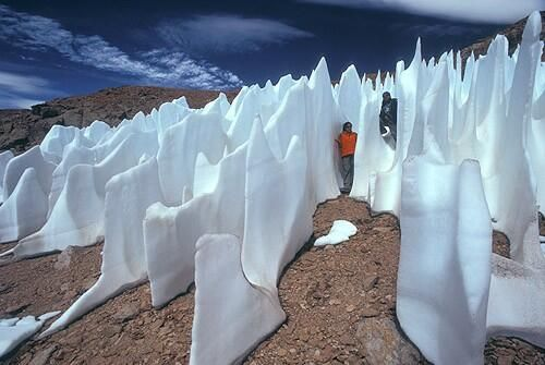 """Atacama penitentes, Chile: """"The snow undergoes a process of sublimation – when ice changes directly to gas without changing to water first. The sublimation causes pits in snow that hollow out to deeper caverns. When ice sublimates in the caverns, it turns to mist – and makes the climate in the cavern wet enough for liquid to form."""" *Click for more, including a video."""