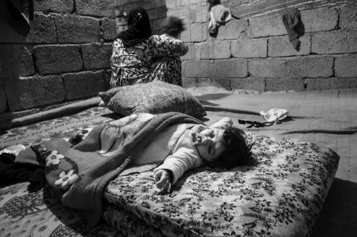 A baby girl sleeps on a mattress in the room that has become home for her family. Originating from the town of Deir ez-Zur in eastern #Syria, her family is one of four living in a partially-constructed home. About 30 people share the cold, draughty space in Erbil. © UNHCR/B.Sokol