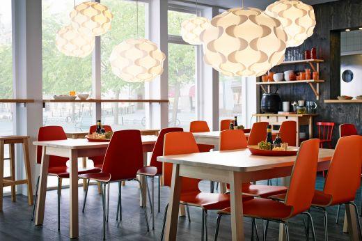 Restaurante decorado com mesas em bétula com velatura branca, com cadeiras em laranja e pernas cromadas