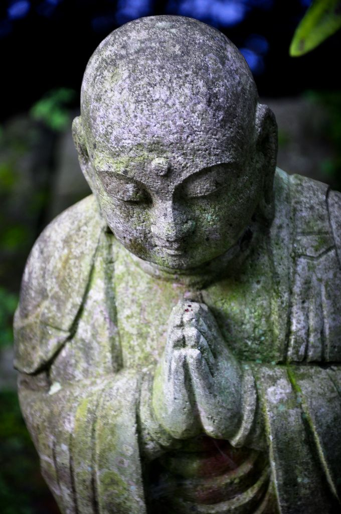 A small Buddhist statute of a monk in prayer.  This photo was taken at Hase-dera, a temple in Kamakura, Kanagawa prefecture, Japan.