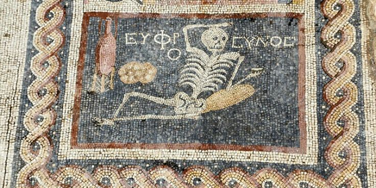 """A Hatay nella città di Antiochia in Turchia, al confine con la Siria, è stato ritrovato questo mosaico che risale a 2400 anni fa. Uno scheletro seduto in una posizione rilassata con in mano una tazza, un'anfora per vino e un pezzo di pane. Alle sue spalle la scritta in greco antico """"Goditi la vita"""". In realtà la scoperta del mosaico risale al 2012 ma solo la settimana scorsa è stata ufficializzata dall'agenzia statale Andalou Agency. Il mosaico fa parte di un gruppo di mosaici che gli…"""