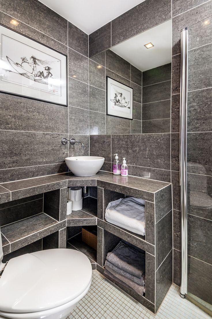 Et lekker bad med mørke fliser på veggen.