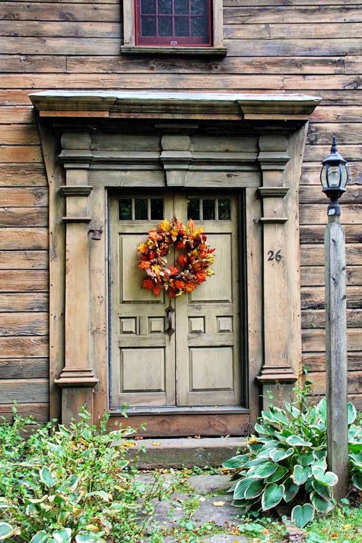 This distressed wood house with the green door and a Fall Wreath; rustic beauty.