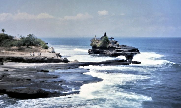 Spectacular Tanah Lot temple on the coast of Bali, Indonesia in 1975. The surf is rumbling from the Indian Ocean. Temple visitors walk across the rocks to visit at low tide.